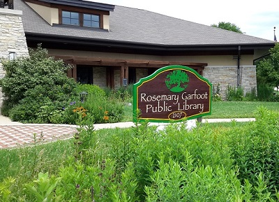 Photo outside the library featuring the library sign and a natural planting