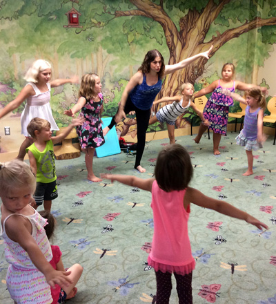 Yoga teach with children in a circle pretending to be flying airplanes.