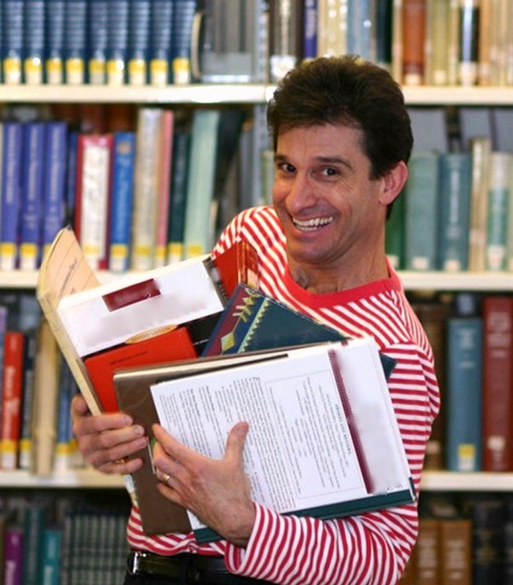 Chris Fascione holding lots of books and smiling at the camera.