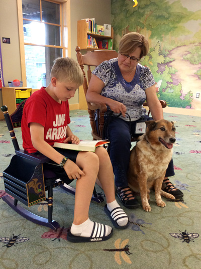 Boy reading to dog and dog owner.