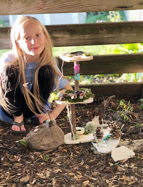 girl with her newly-made fairy house in her yard.