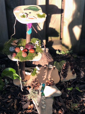 Fairy house with moss, leaves, rocks, branches, pinecones, and other natural items.