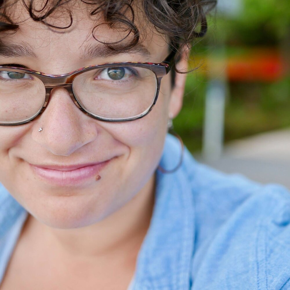 Close up smiling face of Sarina Partridge showing glasses, curly brown hair