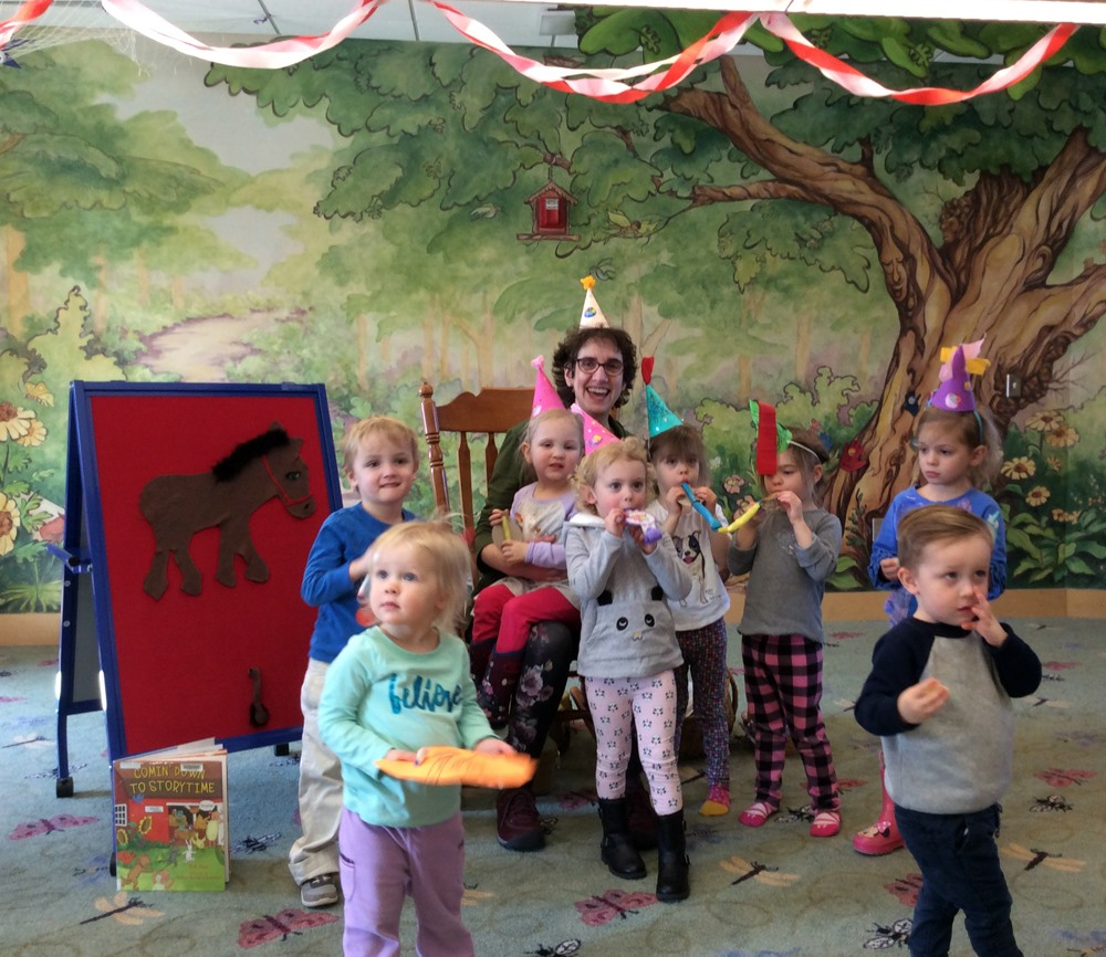 Librarian, Catherine with group of children all in party hats, sitting in front of woodland mural.
