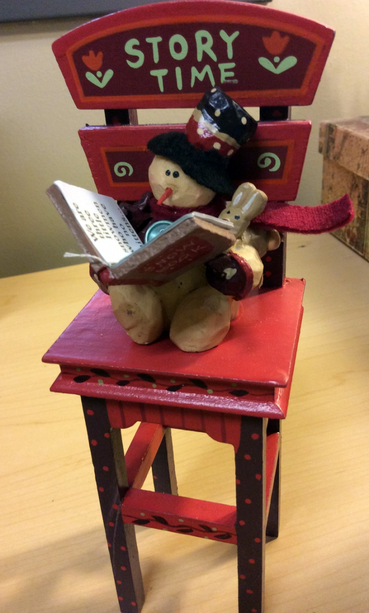 Story Time wooden snowman sitting and reading in a tall chair