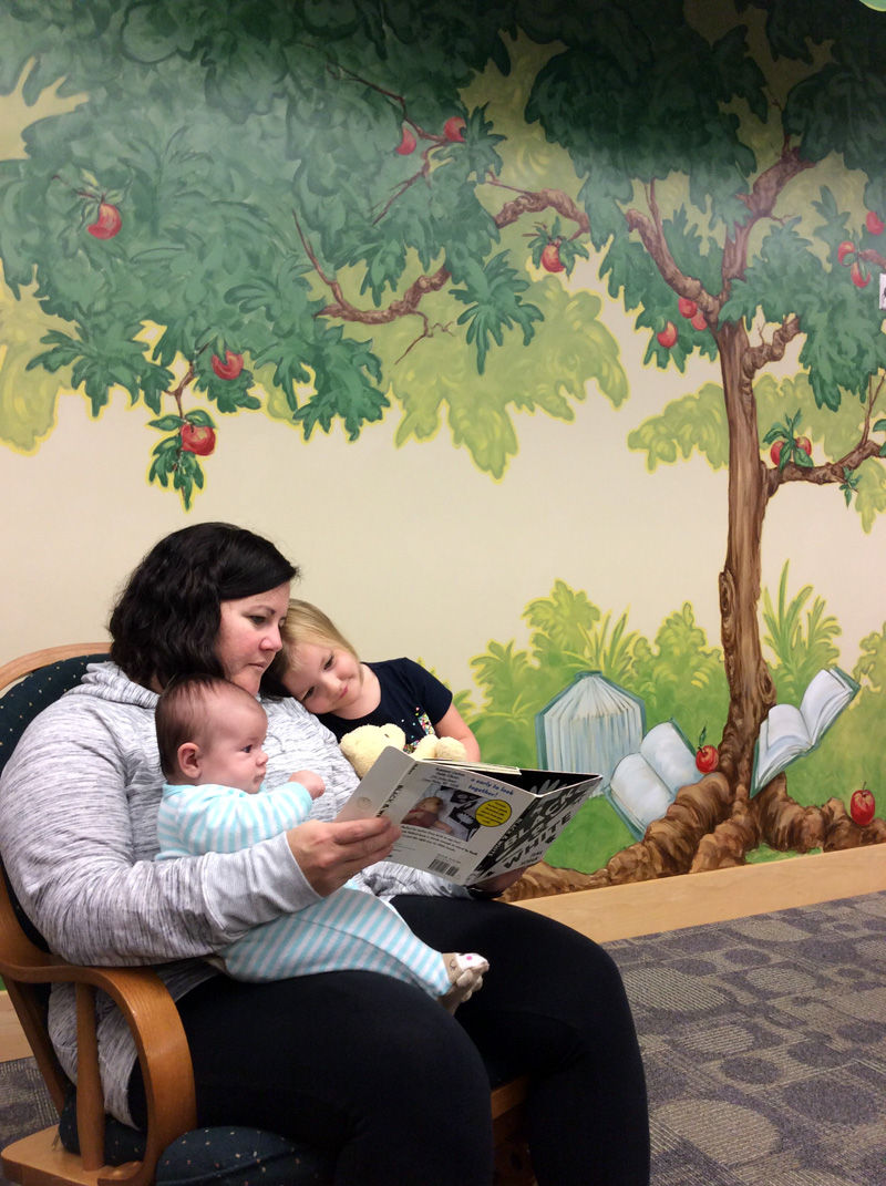Mom reads to young daughter and baby in a rocking chair in front of apple tree mural.