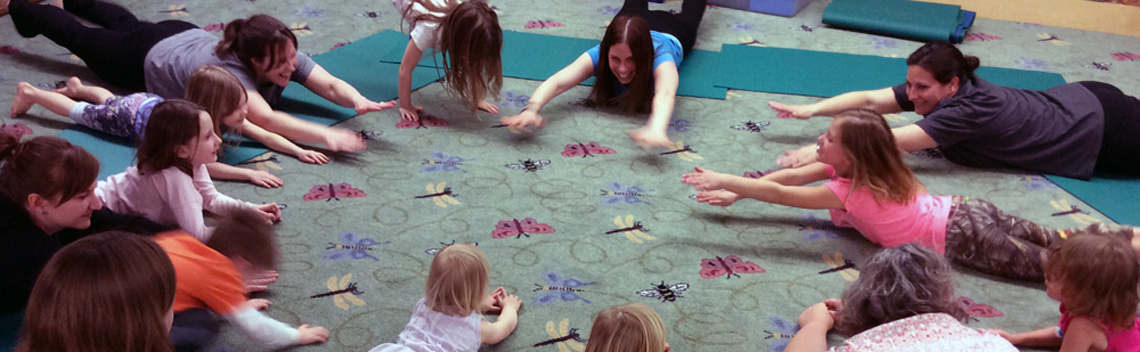 Circle of kids and moms stretching on the storytime room carpet.
