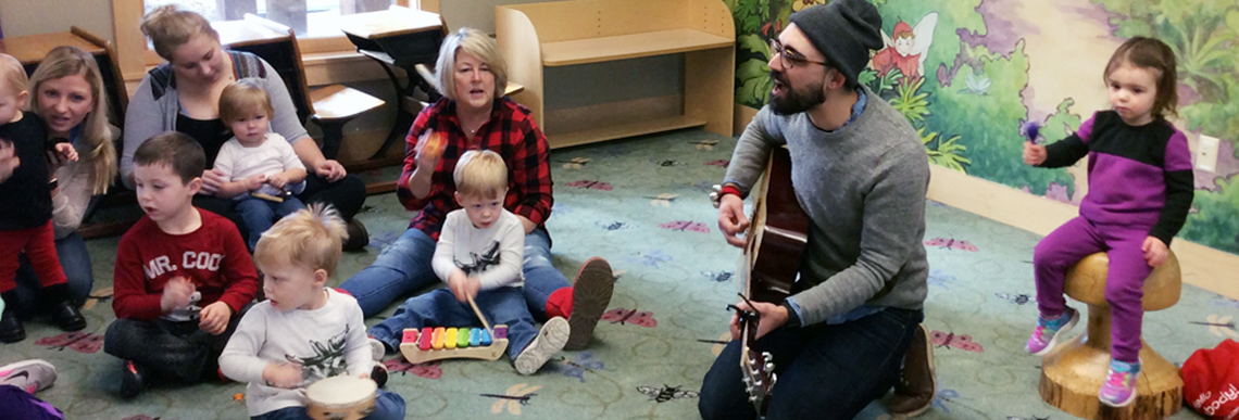 Corey Hart plays the guitar with children and their caregivers.