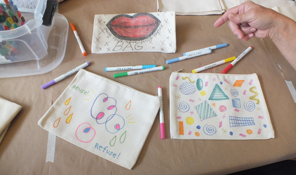 3 cloth bags with colorful drawings and markers.
