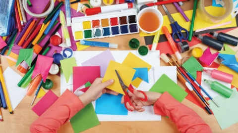 A lot of colorful crafting supplies and a pair of children's hands cutting yellow paper.