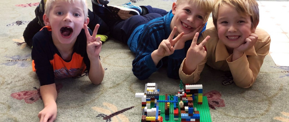 Three boys with their Lego creation.