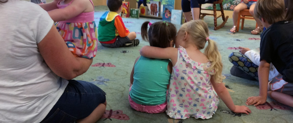two little girls, one with her arm around the other's shoulders, listen to stories